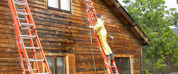 Preserving log homes - working on side of log home | Log Home Contractors California